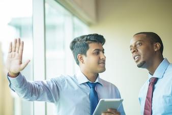 Dois empresários usando tela transparente