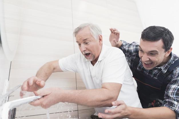 Dois encanadores consertam a torneira do banheiro.