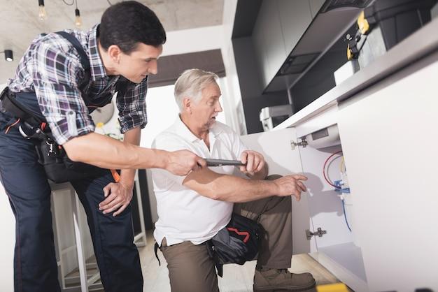 Dois encanadores na cozinha que repara a banca da água.