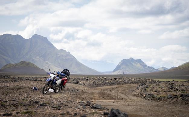 Dois enduro motocicleta em pé em uma estrada de terra no deserto, cercada por montanhas na trilha laugavegur, islândia. conceito de viagens off road, equipamento de piloto de enduro, estilo de vida extremo.