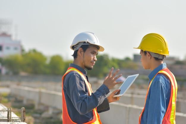 Dois engenheiro falando comunicação usam tablet inspeção no canteiro de obras