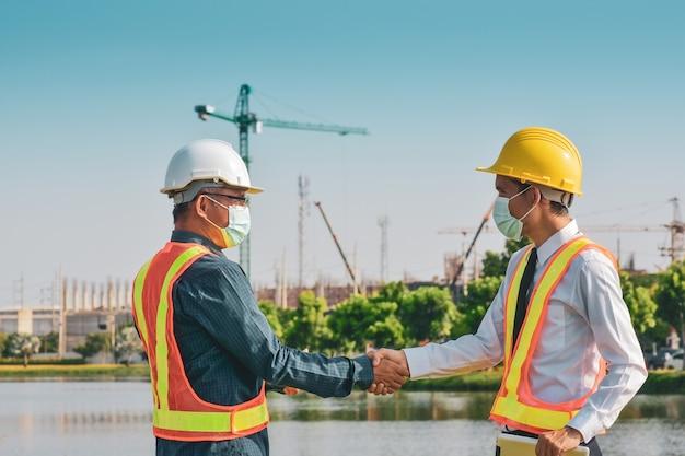 Dois engenheiros apertam a mão na construção do local
