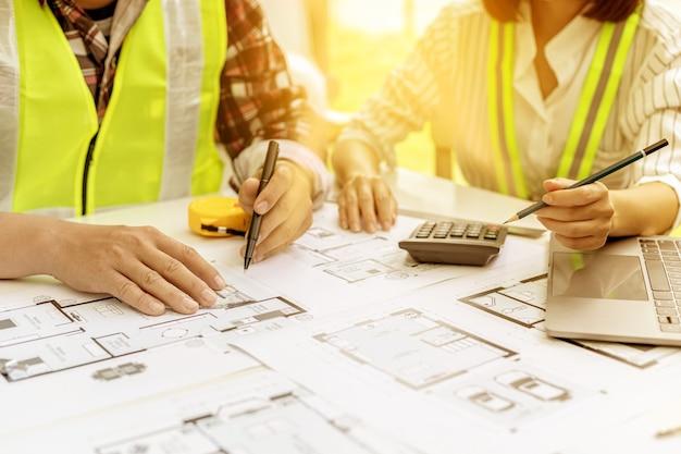 Dois engenheiros-arquitetos fazem consultoria para modificar as plantas da casa contratada, eles têm uma reunião para inspecionar os projetos da casa antes de se reunir com o cliente. idéias de design para casa.