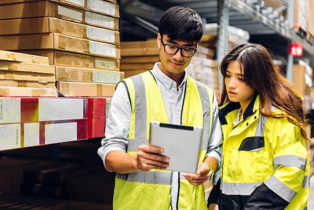 Dois engenheiros asiáticos na equipe de capacetes solicitam detalhes em um tablet para verificar produtos e suprimentos