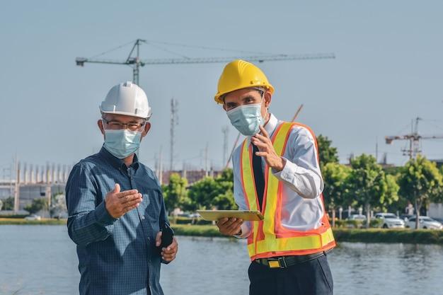 Dois engenheiros com máscara facial falando planejamento de projeto na construção do local