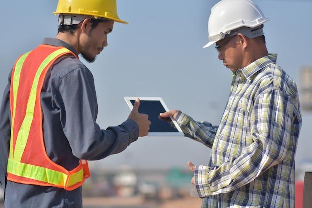 Dois engenheiros conversando ao ar livre