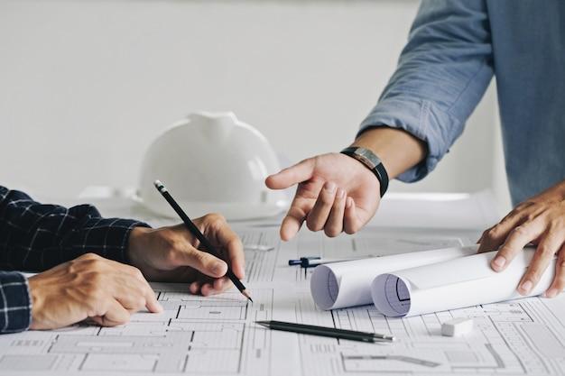 Dois engenheiros de canteiro de obras de homem de negócios trabalhando com desenho na planta e discutindo o chão