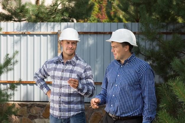 Dois engenheiros de canteiro em uma pausa para fumar juntos em seus capacetes à sombra de uma árvore em um canteiro de obras