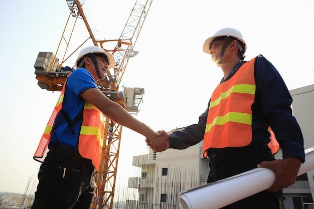 Dois engenheiros de construção apertem as mãos no canteiro de obras