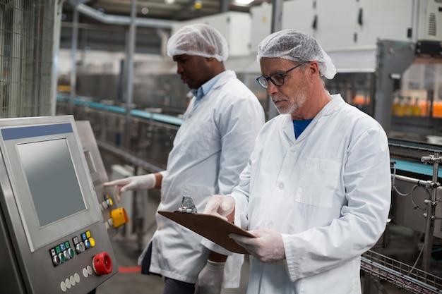 Dois engenheiros de fábrica, operando a máquina na fábrica