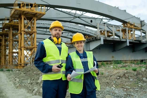 Dois engenheiros de sucesso em roupas de trabalho em pé contra uma grande estrutura de construção