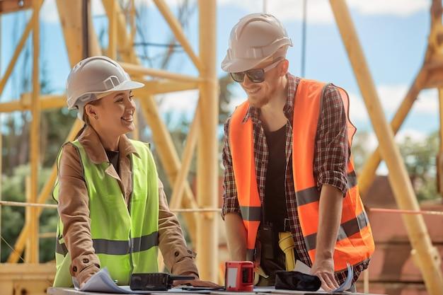 Dois engenheiros discutem o processo de construção de acordo com um desenho contra o de um guindaste de torre de construção