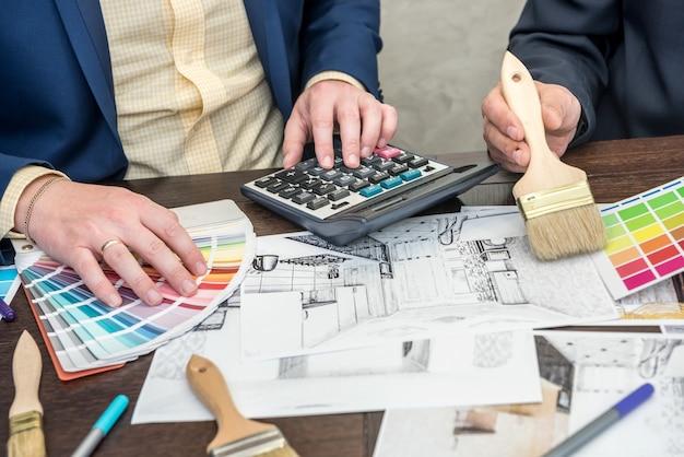 Dois engenheiros discutindo plantas de apartamentos trabalhando na escolha de cores em paletes e laptop. local de trabalho criativo
