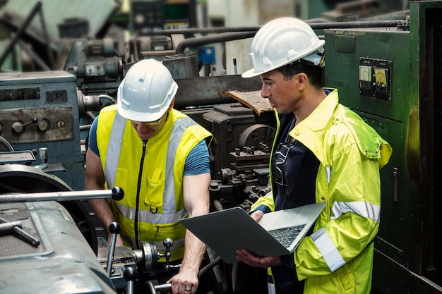 Dois engenheiros do sexo masculino planejando produzir peças automotivas com máquinas em uma fábrica na tailândia.