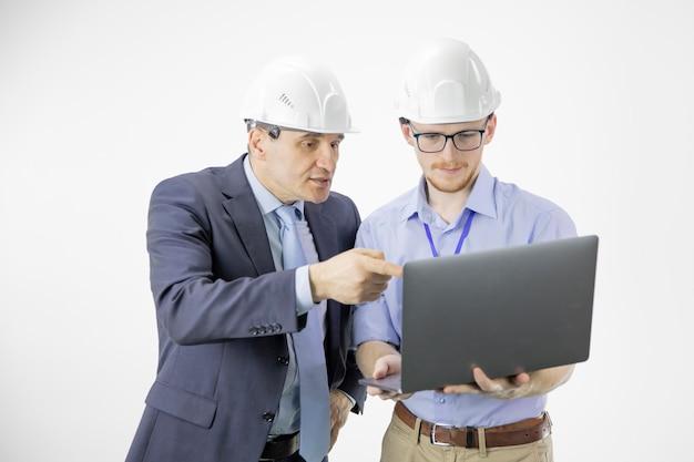 Dois engenheiros em capacetes discutem novo projeto enquanto usam laptop