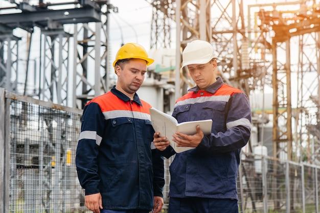 Dois engenheiros especializados em subestações elétricas inspecionam equipamentos modernos de alta tensão à noite. energia. indústria.