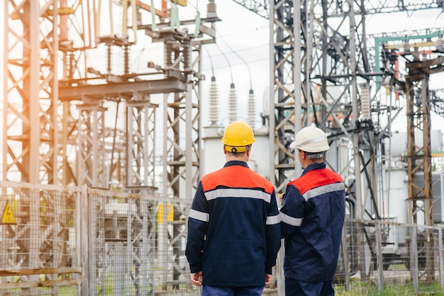 Dois engenheiros especializados em subestações elétricas inspecionam equipamentos modernos de alta tensão durante o pôr do sol. energia. indústria.