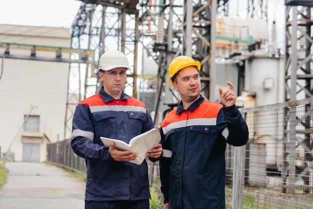 Dois engenheiros especializados em subestações elétricas inspecionam equipamentos modernos de alta tensão. energia. indústria.