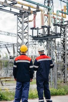 Dois engenheiros especializados em subestações elétricas inspecionam equipamentos modernos de alta tensão.