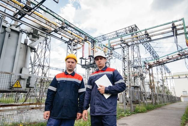Dois engenheiros especializados em subestações elétricas inspecionam equipamentos modernos de alta tensão