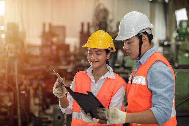 Dois engenheiros, homens e mulheres trabalhando juntos, jovens asiáticos trabalham em equipe e ajudam a manter juntos um sorriso feliz na indústria pesada de fábrica