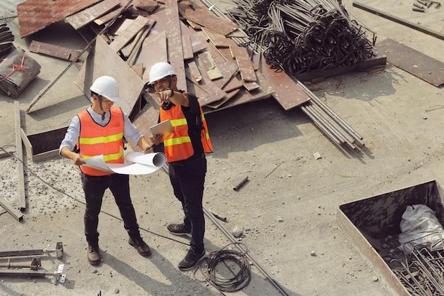 Dois engenheiros trabalham no canteiro de obras. eles estão verificando o andamento do trabalho.
