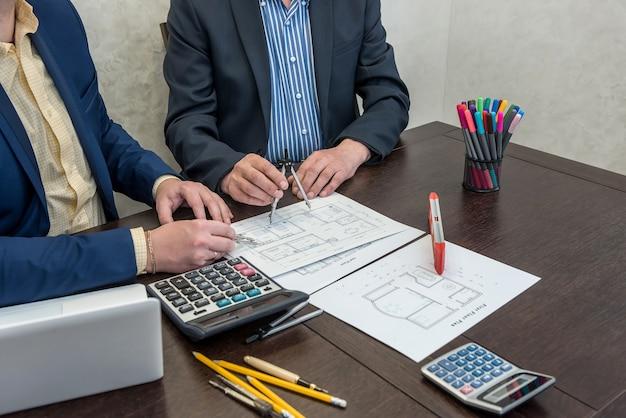Dois engenheiros trabalhando em conjunto com a planta da casa de arquitetura na mesa de escritório com laptop e ferramentas. novo design moderno de casa