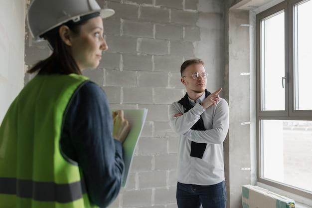 Dois engenheiros, um homem e uma mulher, com capacetes brancos e coletes protetores verdes