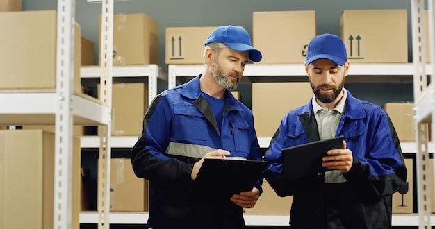 Dois entregador de uniforme azul em pé na loja postal e conversando enquanto trabalhava.