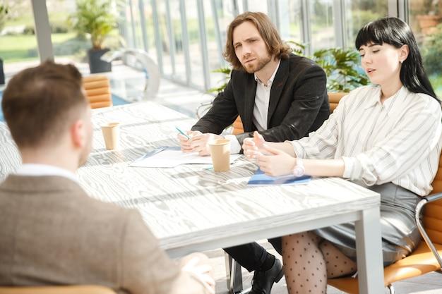 Dois entrevistadores estão questionando um candidato em uma entrevista de emprego