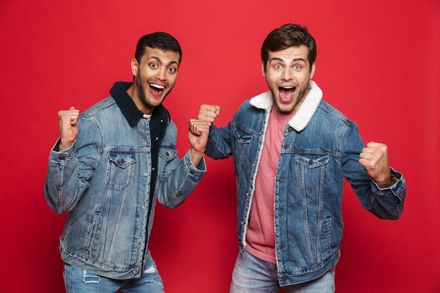 Dois entusiasmados jovens amigos vestindo jaquetas jeans em pé, isolados sobre uma parede vermelha, comemorando
