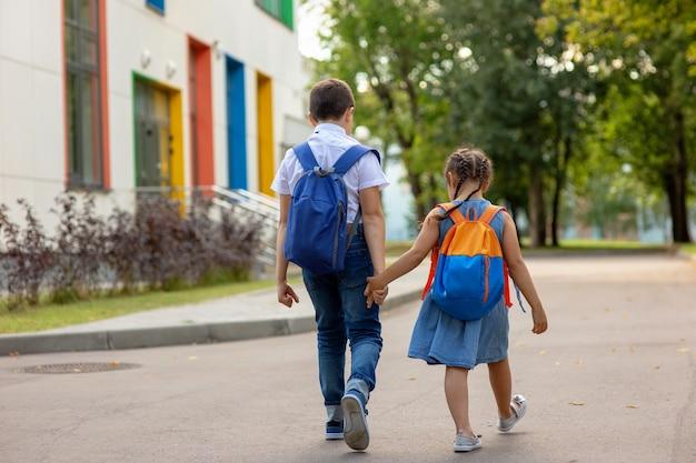 Dois escolares, uma menina e um menino de camisa branca com mochilas vão a caminho da escola