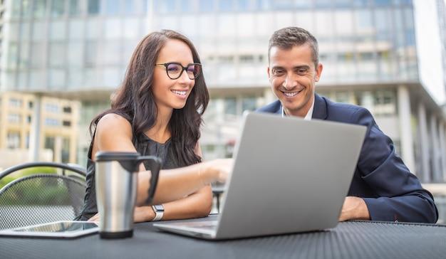 Dois escritórios, administração, finanças ou advogados discutem estratégia de trabalho olhando para um laptop ao ar livre, sorrindo.