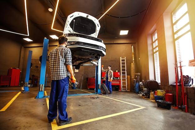 Dois especialistas em uniformes consertando carro juntos na garagem