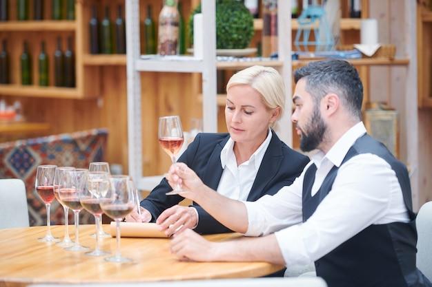 Dois especialistas em vinícolas discutindo características de novos tipos de vinho na adega enquanto um deles faz anotações