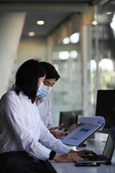 Dois especialistas financeiros em máscara protetora e discutindo informações durante o processo de contabilidade no escritório.