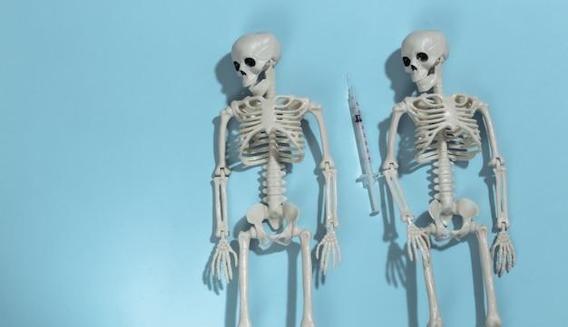 Dois esqueleto e seringa sobre um fundo azul brilhante. dependência de drogas.