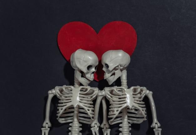 Dois esqueletos de amantes e coração decorativo vermelho sobre fundo preto. dia dos namorados ou tema de halloween.