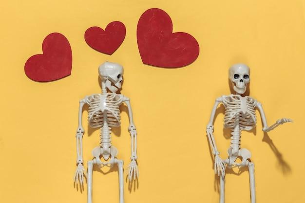 Dois esqueletos e corações decorativos vermelhos em um fundo amarelo brilhante. dia dos namorados ou tema de halloween.
