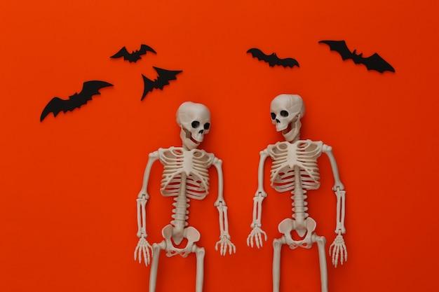 Dois esqueletos e morcegos em laranja brilhante. decoração de halloween, tema assustador
