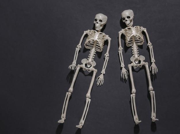 Dois esqueletos em fundo preto escuro.