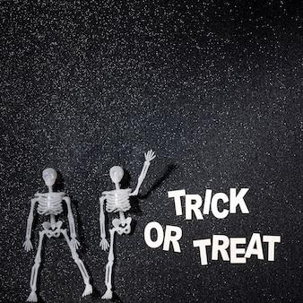 Dois esqueletos em uma composição de doces ou travessuras