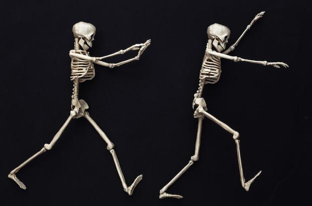 Dois esqueletos falsos em preto. decoração de halloween, tema assustador