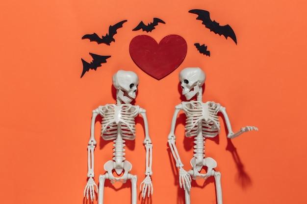 Dois esqueletos, morcegos e coração decorativo vermelho em um fundo laranja brilhante. dia dos namorados ou tema de halloween.