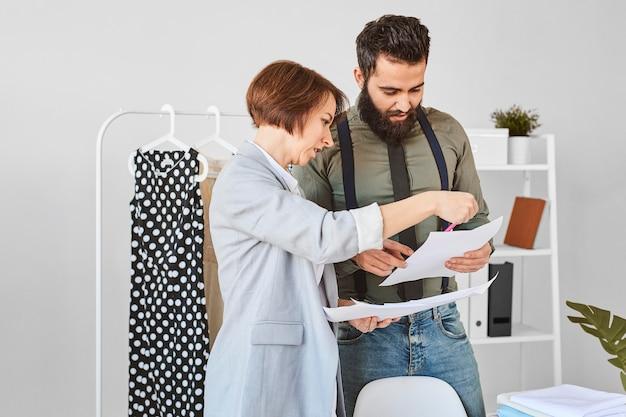 Dois estilistas em ateliê consultando planos de linha de roupas