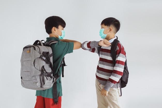 Dois estudante asiático com máscara médica fazendo cotovelada evitando o vírus corona