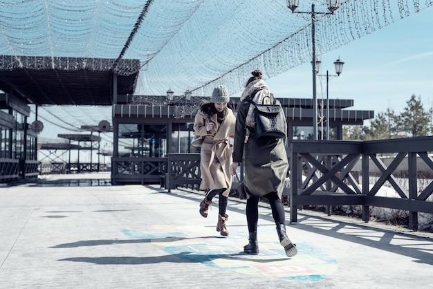 Dois estudantes andam na rua e jogam amarelinha no asfalto, juventude, infância
