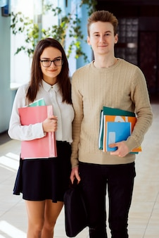 Dois estudantes animados com bolsa para laptop e livros em pé no corredor da universidade antes de começar as aulas