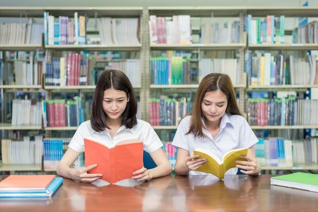 Dois estudantes asiáticos que estudam junto na biblioteca na universidade.