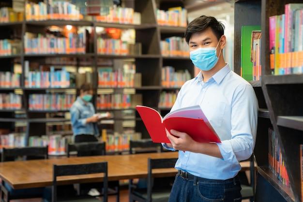 Dois estudantes asiáticos usando máscara facial e de pé na biblioteca a uma distância social de outros 6 pés